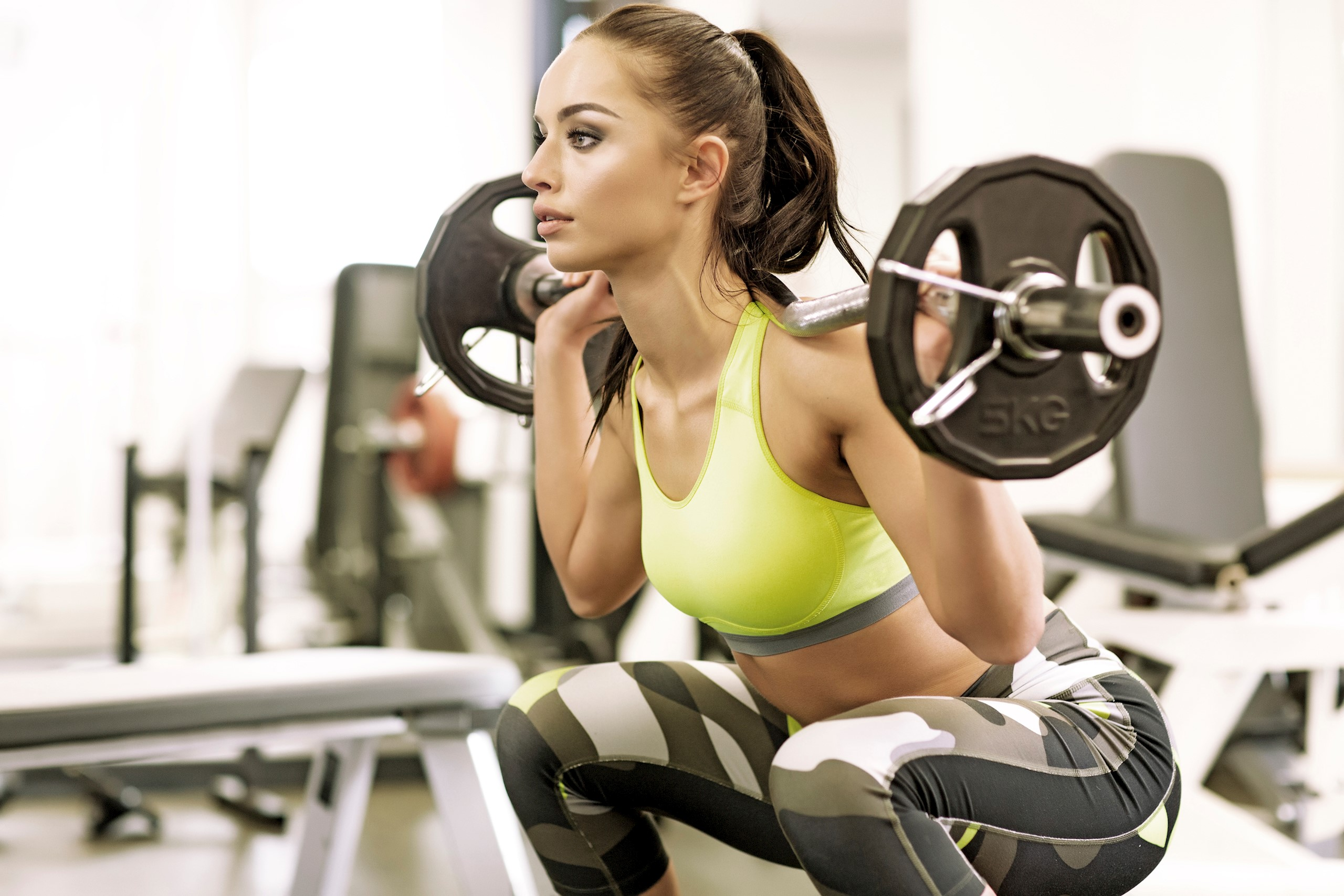Brunette female working out with weights at a gym